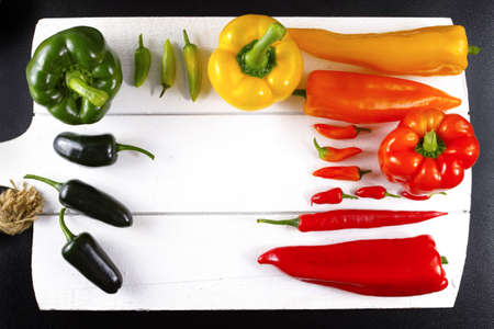 piquancy: Mexican hot chili peppers colorful mix paprika poblano serrano jalapeno on white wooden board Stock Photo