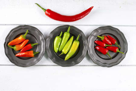 piquancy: Mexican red green orange hot chili peppers colorful mix jalapeno on metal bowls
