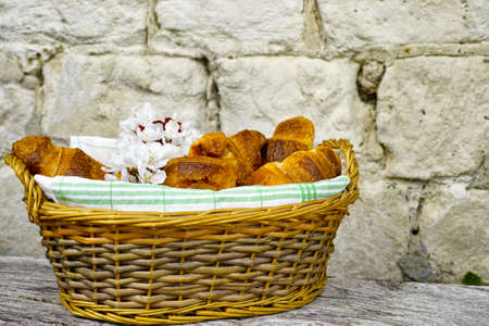 traditionally french: Fresh french croissants in a basket from bakery on background with old stone wall