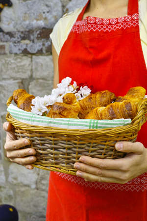 picnick: Young woman in red apron holding a wicker basket of fresh baked croissants