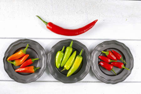 red jalapeno: Mexican red green orange hot chili peppers colorful mix jalapeno on metal bowls