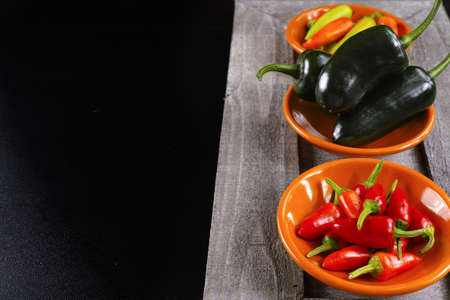 piquancy: Mexican hot chili peppers colorful mix jalapeno on orange bowls and black background