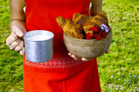 picnick: Young woman in red apron holding farm milk and fresh baked croissants Stock Photo