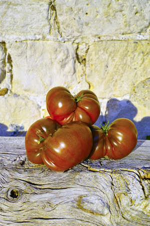 heirloom: Big Black Heirloom organic tomatoes on wooden and stone background Stock Photo