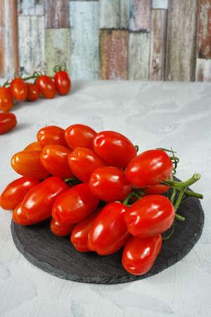 Roma: Fresh ripe mini roma tomatoes on grey board