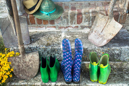 rubber boots: Garden equipment - rubber boots, schovels and srtaw hats in sunny day on old stone wall background Stock Photo