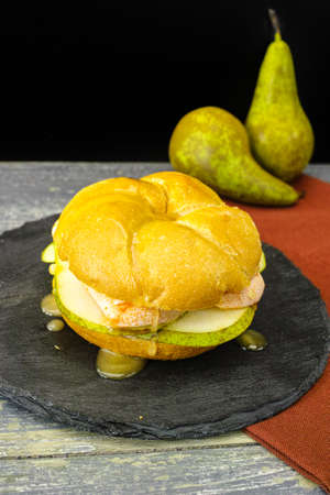honing: Healthy Vegetarian Veggie Sandwich with French soft cheese, pear and honing on black stone plate Stock Photo
