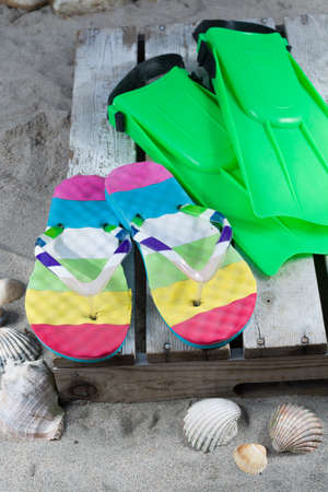 sports shell: Two green flippers and flops on the sandy beach