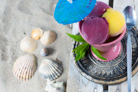 blackcurrant: Mango and black-currant ice-cream in pink cone on the beach on old wooden background Stock Photo