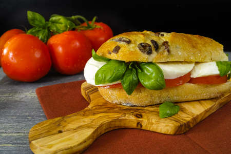 quick snack: Healthy Vegetarian Veggie Sandwich with tomato, basil, mozzarella cheese made with bread with black olives, italian style