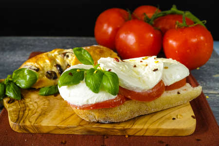black olives: Healthy Vegetarian Veggie Sandwich with tomato, basil, mozzarella cheese made with bread with black olives, italian style