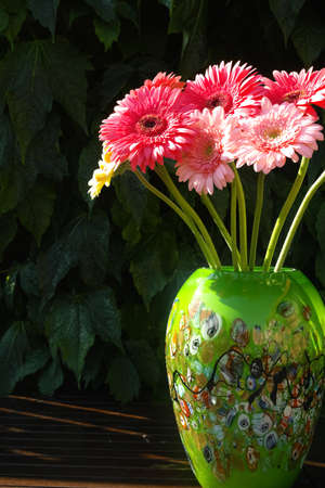 gerbera daisies: Colorful gerbera daisies in green vase made from mozaic murano glass Stock Photo