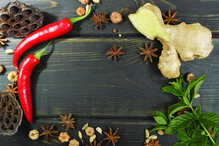 medical decisions: Colorful red hot chili peppers and ginger on black wooden table top Stock Photo