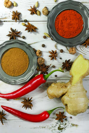 variability: Colorful variety of Indian spices with fresh chili and ginger on white wooden table top Stock Photo