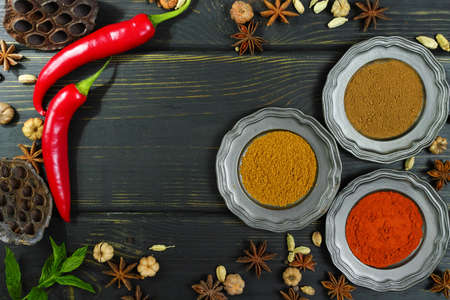 variability: Colorful variety of Indian spices on black wooden table top