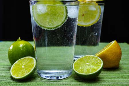 Glas met koud mineraalwater, limoen en citroen, seltzer Stockfoto