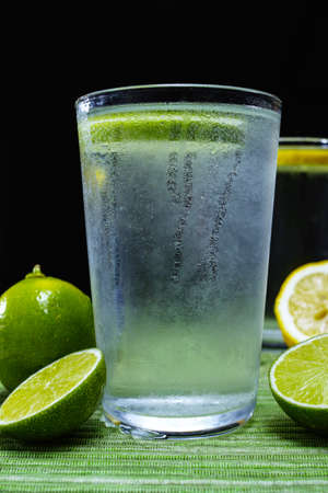 seltzer: Glass with cold sparkling mineral water with fresh green lime, seltzer