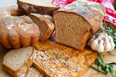 masa fermentada pan de escanda recién horneado a bordo de madera de olivo con granos enteros Foto de archivo