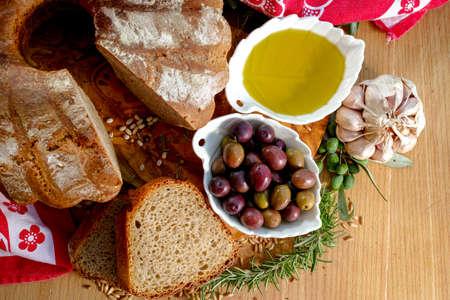 extra virgin olive oil: Freshly baked homemade sourdough spelt bread, extra virgin olive oil and olives on olive wood plank