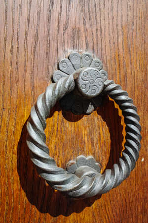 Old ancient door knocker on wooden door, Tuscany, Italy