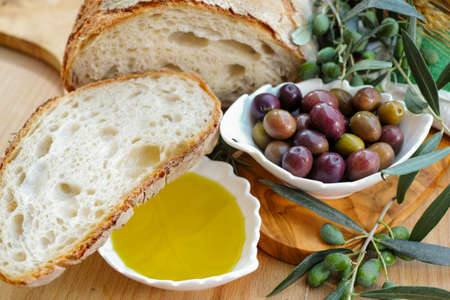 Traditional italian appetizer - fresh homemade bread, extra virgin olive oil and olives on wooden background