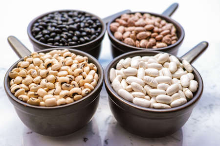 lima beans white beans: Beans variety different types of beans in ceramoc bowls on black wooden background