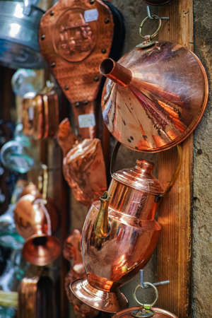 pienza: Copper kitchenware hanging on the wall in the shop, Pienza, italy Stock Photo