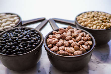 turtle bean: Beans variety different types of beans in ceramoc bowls on black wooden background