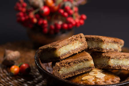 speculaas: Fresh Dutch filled spicy  cookies with almonds on autumn colored and dark background Stock Photo