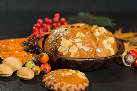 speculaas: Typical Dutch filled spicy  cookies with almonds on autumn colored and dark background