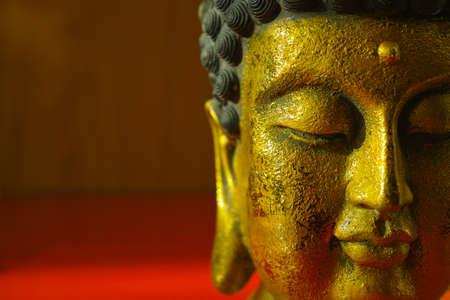Gouden Boeddha gezicht op donkerrode achtergrond
