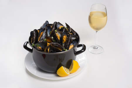 North Sea fresh steamed mussels in black pan, tasty seasonal food with lemon