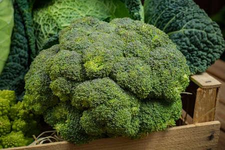 Green and orange fresh vegetables in wooden box, harvest - broccoli, savoy cabbage, green cauliflower, carrot, pumpkin