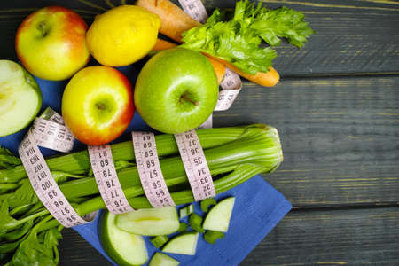 centimetre: Green vegetables and fruits -  celery shoots and  apples, healthy fitness diet concept