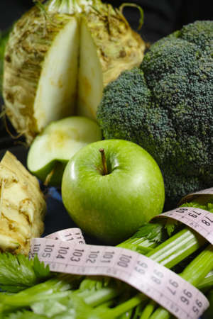 Green vegetables and fruits -  celeriac, broccoli, celery shoots and  apples, healthy fitness diet concept