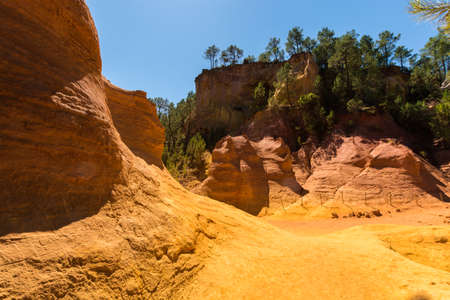 Oragne ochre picturesque hills. Languedoc - Roussillon, Provence, France. Preserve natural dye production - ocher.