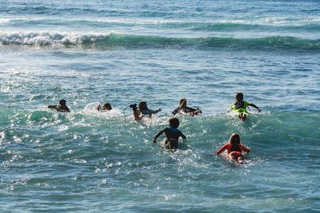 Surf school - several surfboarding students headed into an ocean swell on Tenerife, Spain