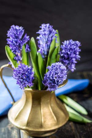 First spring flower - blue hyacinth in brass vase copy space