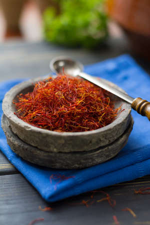 safran: Raw Organic Red Saffron Spice in a clay bowl on wooden table Stock Photo