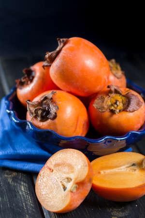 Ripe orange hachiya persimmons in blue bowl Stock Photo