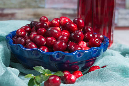 cranberry juice: Red cranberry juice in a glass, cranberries in the blue clay bowl on the table, blue wall Stock Photo