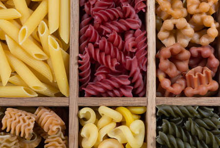 Variety of types, colors and shapes of Italian pasta. Dry pasta background, close up