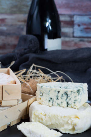 munster: French soft cheeses on black stone platter and bottle with red wine Stock Photo