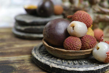 Tropical fruits - Lychees and Passion Fruit or Maracuya, on wooden background