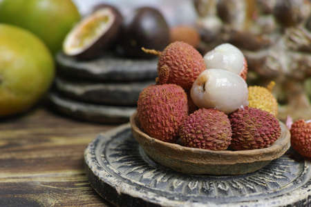 Tropical fruits - Lychees and Passion Fruit or Maracuya and Mango, on wooden background
