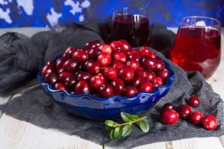 Red cranberry juice in a glass, cranberries in the blue clay bowl on the table, blue wall Stock Photo
