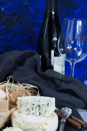 cheeseboard: French soft cheeses on black stone platter and bottle with red wine Stock Photo