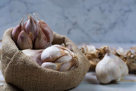 Garlic. Dried French garlic. Red garlic. Violet garlic.Garlic background. garlic bulbs on white marble. Stock Photo