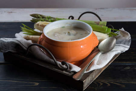 Spring season - white and green fresh asparagus cream- soup, ready to eat with vegetables