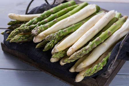 Fresh spring green and white asparagus, ready to cook, on wooden backgroung, close up